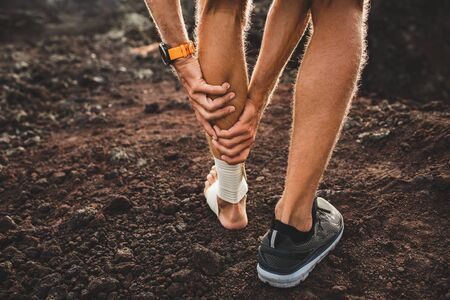 Male runner holding injured calf muscle close-up and suffering with pain. Leg injury. Compression bandage on ankle. View from back. Sprain ligament or tendon while running outdoors. Stock Photo - 127997632
