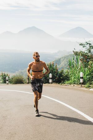 Man running in uphill on the asphalt road in hot summer weather. Panoramic mountain view on background. Using chest heart rate monitor.
