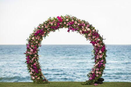 Arco rotondo di nozze decorato con bellissime orchidee colorate e fiori di rosa sulla spiaggia. Oceano sullo sfondo. Archivio Fotografico