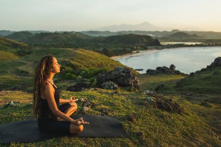 Woman doing yoga alone at sunrise with mountain and ocean view. Harmony with nature. Self-analysis and soul-searching