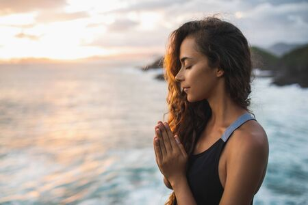 Young woman praying and meditating alone at sunset with beautiful ocean and mountain view. Self-analysis and soul-searching. Spiritual and emotional concept 写真素材