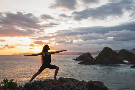 Young slim woman practicing yoga at sunset with beautiful ocean and mountain view. Workout outdoors, sport and well-being concept. Colorful and majestic sunset. 写真素材