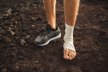 Mans ankle in compression bandage. Leg injury while trail running outdoors. First aid for sprained ligament or tendon. Stock Photo