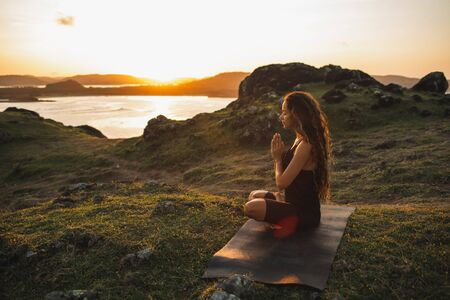 Woman doing yoga alone at sunrise with mountain and ocean view. Harmony with nature. Self-analysis and soul-searching Фото со стока - 130992994
