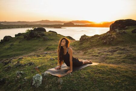 Woman training outdoors on yoga mat at sunrise. Exercise and stretching. Female workout and awakening in morning Фото со стока