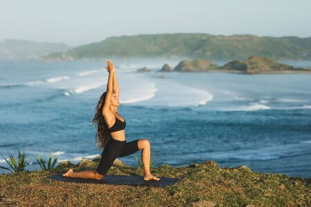 Woman practicing yoga outdoors with amazing ocean and mountain view in morning. Female health and fitness concept. Nature background. Фото со стока - 131123066