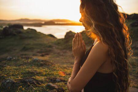 Woman praying alone at sunrise. Nature background. Spiritual and emotional concept. Sensitivity to nature Фото со стока - 131123071