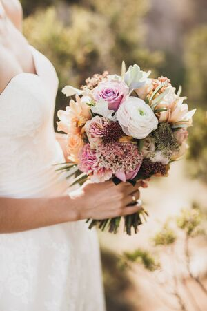 Bride holding in hands small wedding bouquet in orange autumn colors. Pink and orange roses, white peony, dried flowers and leaves.