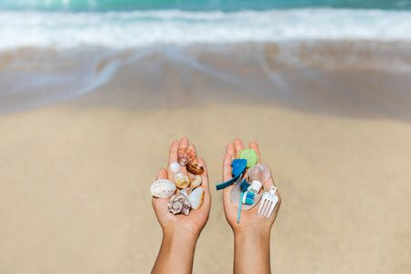 Concept of choice: save nature or continue to use disposable plastic. One hand holding beautiful shells, in the other - plastic waste. Ocean and tropical beach on background. Environmental pollution