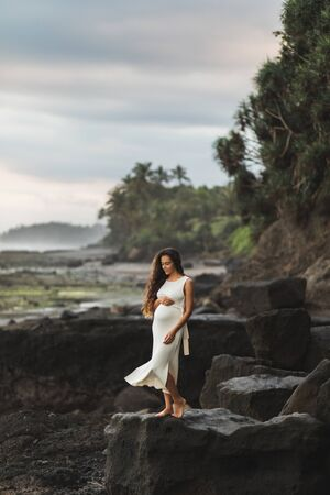 Young pregnant woman in white dress enjoying evening in Bali beach. Sensitivity to nature and harmony. Maternity concept.