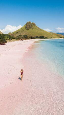 Mujer caminando y disfrutando de la playa tropical paraíso vacío. 16: 9 para el fondo de pantalla del protector de pantalla del teléfono. Vista aérea de la isla de Padar Pink Beach. Foto vertical.