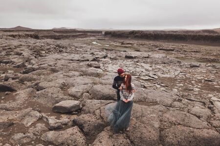 Couple in love walking and kissing in Iceland. Stone volcanic desert around, in the middle of nowhere. Dramatic nordic landscape, cold weather. Wearing in traditional wool sweaters, jeans and skirt. Reklamní fotografie
