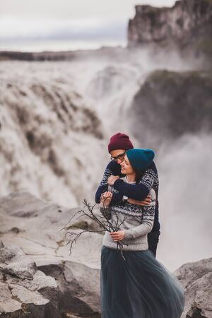 Close up lovely portrait of young hipster couple kissing together near famous Icelandic landscape - Dettifoss powerful waterfall. Traditional handmade wool sweaters, blue and red hats. Reklamní fotografie - 133310203