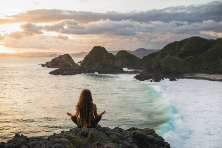 Young woman practicing yoga in lotus pose at sunset with beautiful ocean and mountain view. Sensitivity to nature. Self-analysis and soul-searching. Spiritual and emotional concept.