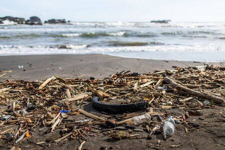 Beach pollution with plastic bottles, rubber tyre and other waste in Bali, Indonesia Stok Fotoğraf