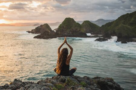 Young woman practicing yoga at sunset with beautiful ocean and mountain view. Sensitivity to nature. Self-analysis and soul-searching. Spiritual and emotional concept. Stock fotó