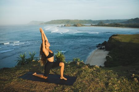 Woman practicing yoga outdoors with amazing ocean and mountain view in morning. Female health and fitness concept. Nature background. Stock fotó
