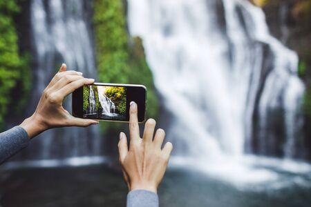Woman hands taking photo of waterfall Banyumala in Bali. Travel concept.