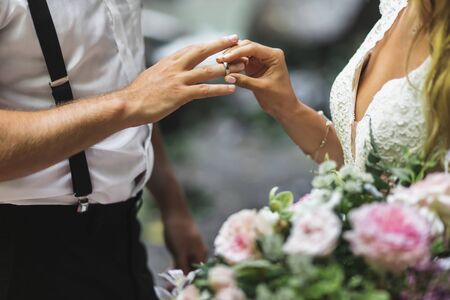 Bride putting wedding ring on grooms hand close up. Symbol of love and commitment.