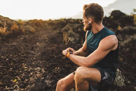Athletic runner start training on fitness tracker or smart watch and looking forward on horizon. Trail running and active lifestyle concept. Stock Photo