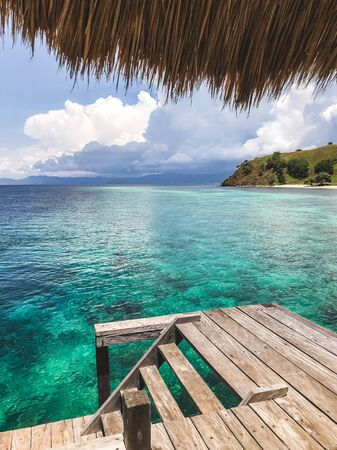View of tropical island with turquoise transparent clear water from wooden pier. Vacations concept. Luxury island resort. Фото со стока - 134620578