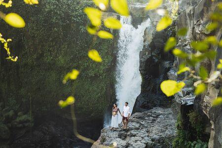 Couple travel in pregnancy. Amazing view of Tegenungan Bali cascade waterfall landscape. Morning sunlight, wanderlust concept Stock Photo