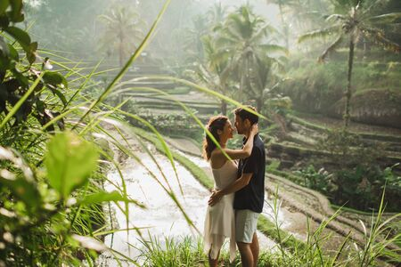 Young latin american couple with amazing view of Ubud rice terraces in morning. Happy together, honeymoon in Bali. Travel lifestyle.