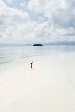 Woman walking alone on amazing tropical white sand beach. Aerial drone view from above. Tropical background and travel concept. Zdjęcie Seryjne