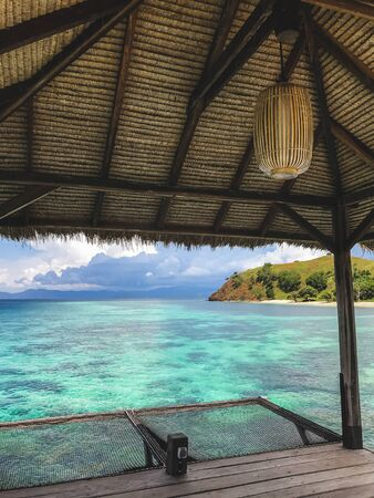View of tropical island with turquoise transparent clear water from wooden pier. Vacations concept. Luxury island resort. Фото со стока - 134974371