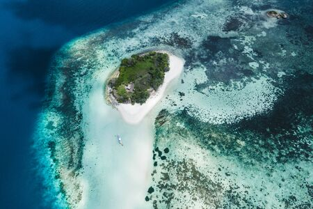 Small coral reef island with white sand beach. Aerial drone view from above. Tropical background. Zdjęcie Seryjne