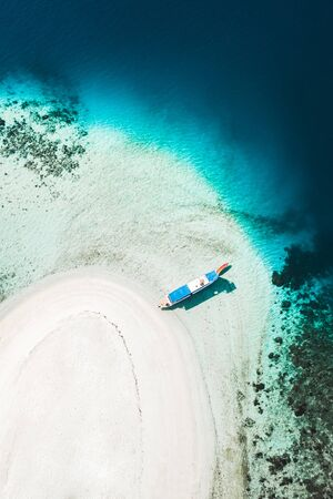 Aerial view of white sand beach on small tropical coral reef island with tourist diving boat. Tropical background and travel concept. Zdjęcie Seryjne