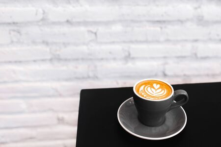 One gray cup of fresh cappuccino on black table. Background of white textured brick wall, loft style interior. Black and white minimalist style. Empty place for text, copy space. Stockfoto