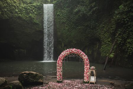 Wedding ceremony on small secret waterfall Tibumana in Bali, Indonesia jungle. Classic round arch with pink and white roses. Unusual destination for wedding.