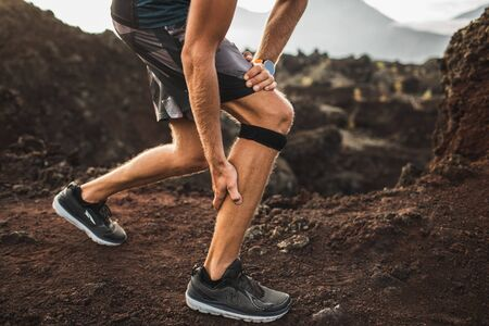 Runner using Knee support bandage but have a problem with calf muscle on running. Leg injury. Stock Photo
