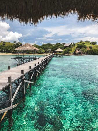 View of tropical island with turquoise transparent clear water from wooden pier. Vacations concept. Luxury island resort. Stock Photo