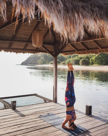 Young woman practicing headstand yoga pose in morning with amazing tropical island view. Luxury retreat, healthy sport lifestyle concept.