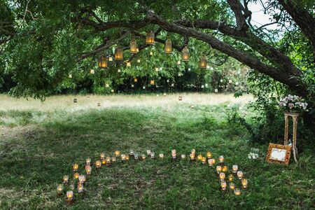 Evening wedding ceremony with a lot of vintage lanterns, lamps, candles. Unusual outdoor ceremony decoration. Beautiful garden party concept. Standard-Bild