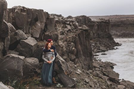 Couple in love walking in Iceland. View of Jokulsa a Fjollum river canyon in cold and gray autumn weather. Amazing nordic landscape. Wearing in traditional wool sweaters, jeans and gray skirt.
