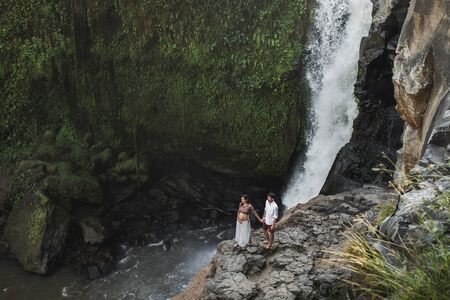 Couple travel in pregnancy. Amazing view of Tegenungan Bali cascade waterfall landscape. Morning sunlight, wanderlust concept Stock fotó