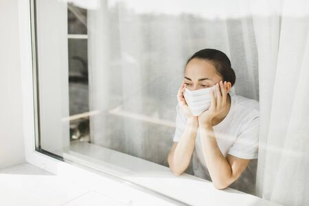 Tired doctor in medical mask looking through window. Important job and self isolation during coronavirus pandemic. Hope for medicine.