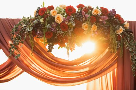 Wooden wedding arch decoration on outdoor sunset ceremony. Red and beige rose flowers, grape and hanging cloth. Amazing warm sun light. Stock Photo