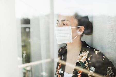Self isolation in coronavirus quarantine. Woman in medical mask looking through window with hope. Prevention of virus spread.