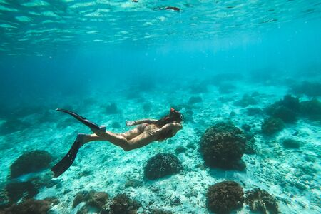Woman snorkelling underwater with snorkel mask in clear transparent water in beautiful tropical lagoon with coral reef. Freediving activity. Leisure on vacations. Stok Fotoğraf