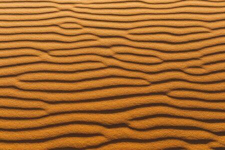 Orange texture of sand dune. Abstract shape, background, shadow and sun light. Sahara desert.