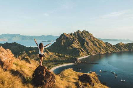 Woman with amazing view of Padar island in Komodo national park, Indonesia. Enjoying tropical vacation in Asia. Lifestyle travel concept. View from behind.