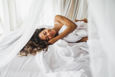Beautiful tanned young woman awakening in white bed. Happy wake up and start new day. Leisure and rest. Wellbeing and carefree concept. Long curly hair. Stay home.