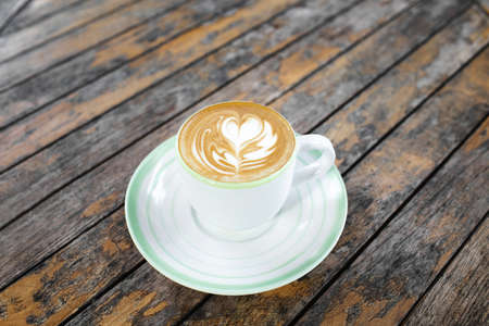 Cup of fresh creamy cappuccino with latte art on foam. Background of brown wooden table with shabby aged surface. View from above.