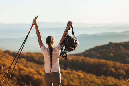 Woman happy to hike top of mountain and hold trekking poles. Nordic walking outdoors, view from behind. Travel lifestyle. Success goal achievement. Standard-Bild