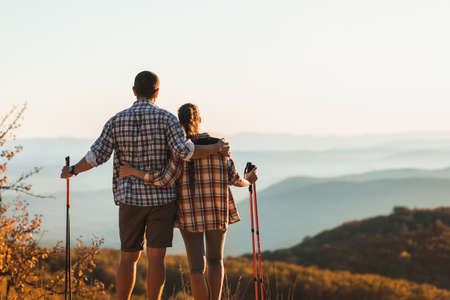 Couple hiking in autumn mountains with trekking sticks. Nordic walking outdoors, view from behind. Travel lifestyle.