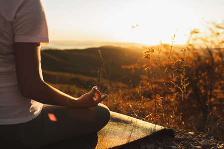Woman hand in lotus position closeup. Zen meditation. Healthy lifestyle and yoga concept. Background of warm sunlight and mountain view. Empty place.